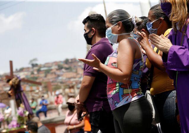 Pessoas rezam perto de uma réplica da estátua do Nazareno de São Paulo em uma rua da favela de Antimano durante uma procissão religiosa, apesar da quarentena nacional devido ao surto do coronavírus em Caracas, Venezuela, 8 de abril de 2020