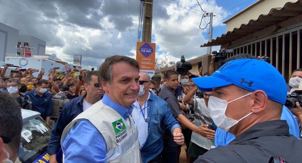 Presidente Jair Bolsonaro acena para apoiadores durante visita ao hospital de campanha em obras em Águas Lindas, em Goiás