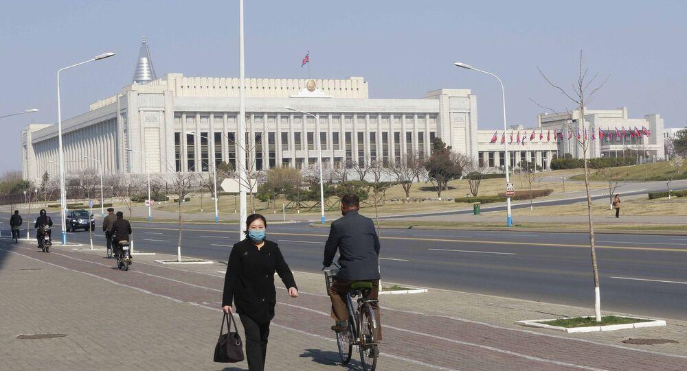 Pessoas caminham em frente ao Parlamento da Coreia do Norte