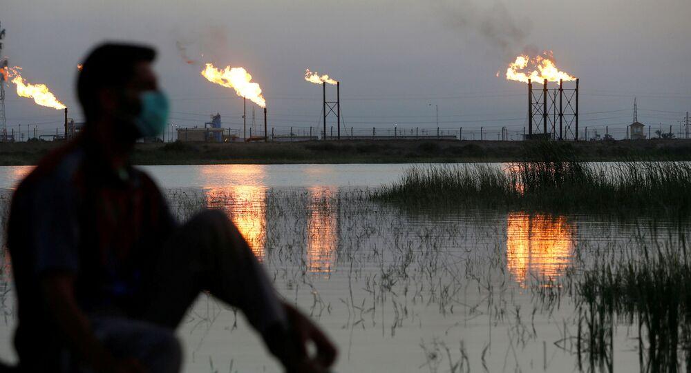 Chamas saem de torres de extração no campo petrolífero de Nahr Bin Umar, sendo visto um homem usando máscara facial protetora, após o surto do coronavírus, ao norte de Basra, Iraque