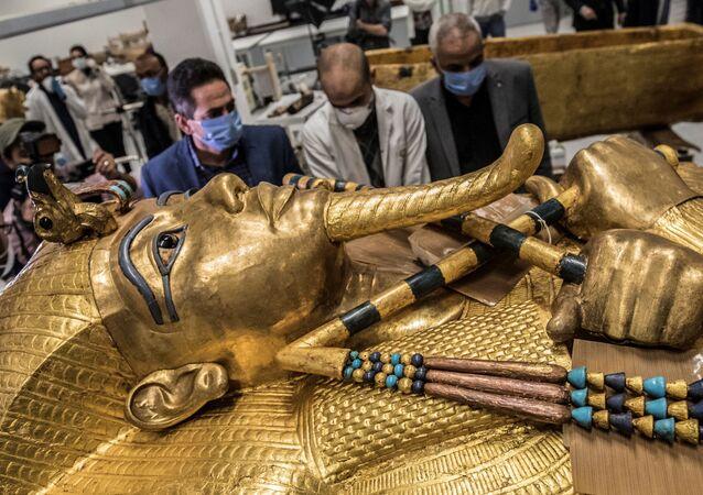 Imagem retrata homens diante de sarcófago dourado do faraó Tutancâmon