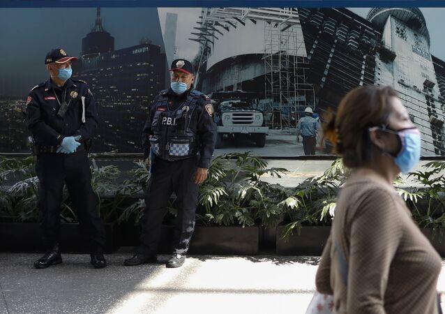 Policiais e pedestre com máscaras para se proteger do coronavírus no México