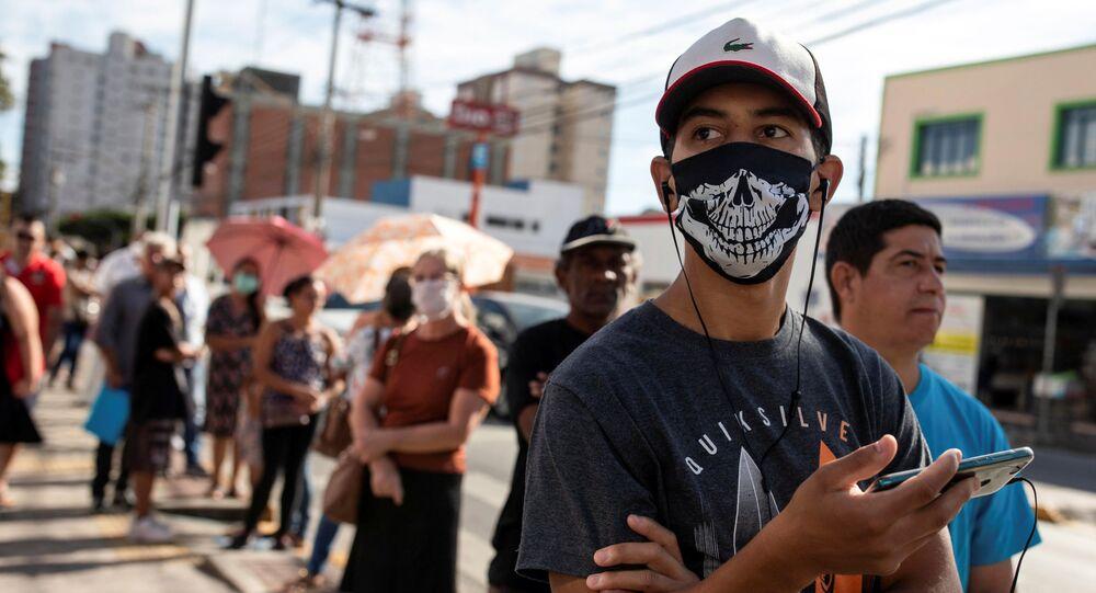 Pessoas fazem fila em frente à agência da Caixa Econômica Federal para receber auxílio emergencial, em Jacareí, São Paulo, 15 de abril de 2020