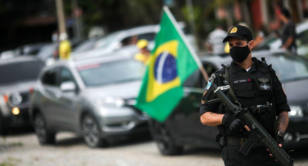 Policial usa máscara durante carreata contra medida de isolamento, no Rio de Janeiro, 15 de abril de 2020