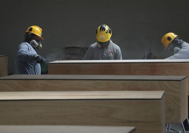 Funcionários públicos preparam caixões para famílias pobres enterrarem entes queridos, mortos por COVID-19, Equador