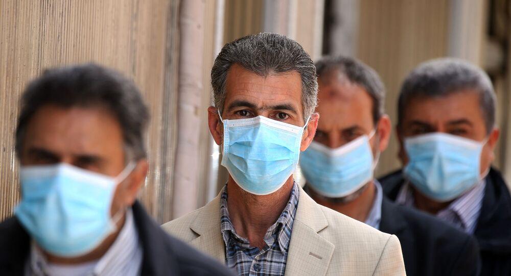 Líbios usando máscaras protetoras fazem fila em frente à agência bancária, na cidade de Trípoli, 1º de abril de 2020