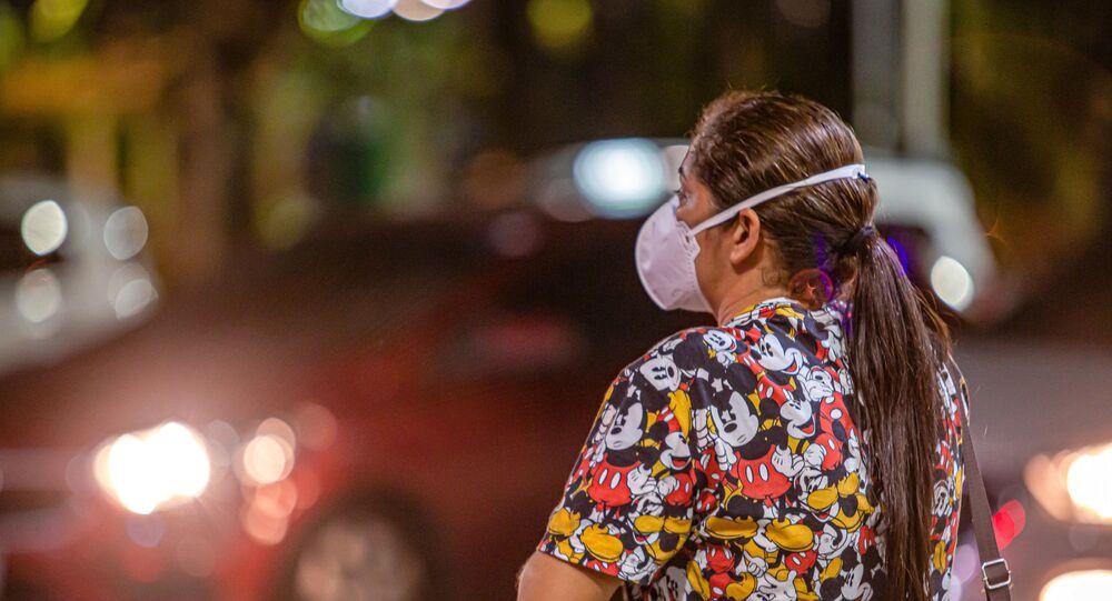 Mulher caminha por rua de Fortaleza, no Ceará, com máscara para se proteger do novo coronavírus