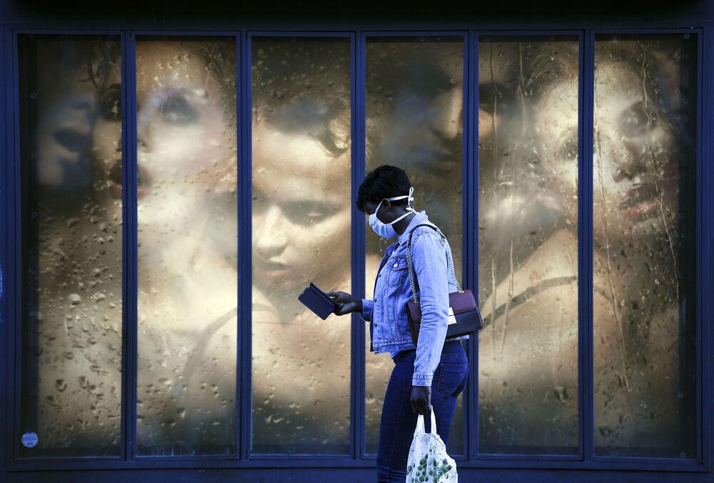 Mulher com máscara protetora passa por vitrine de loja em Paris durante pandemia, França, 14 de abril de 2020