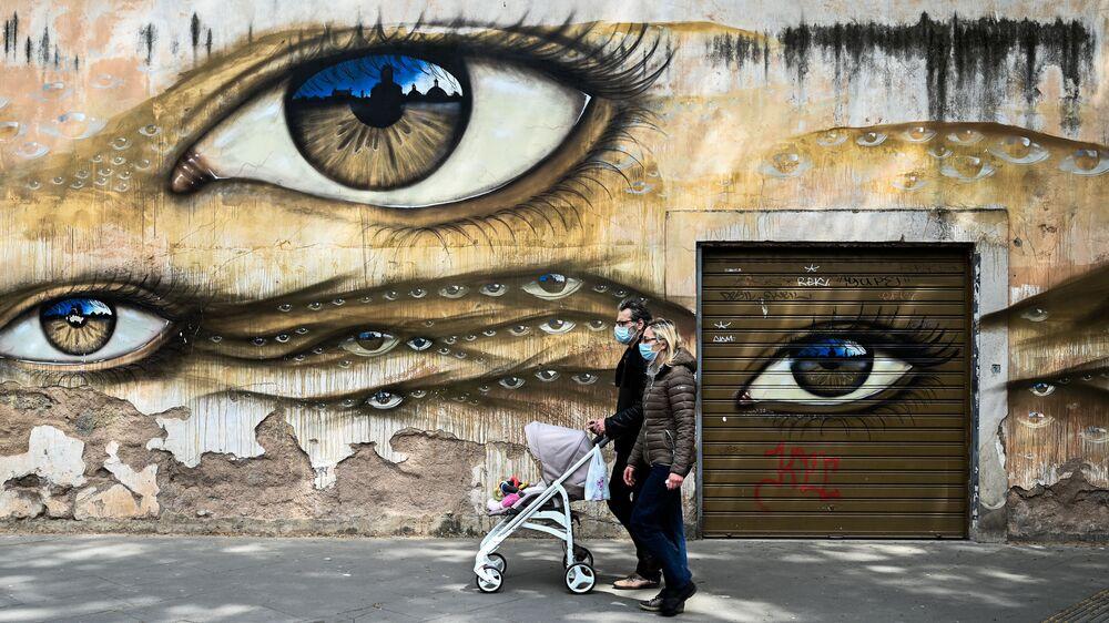 Casal usando máscaras e empurrando carrinho de bebê passa por muro grafitado em Roma, Itália, 13 de abril de 2020