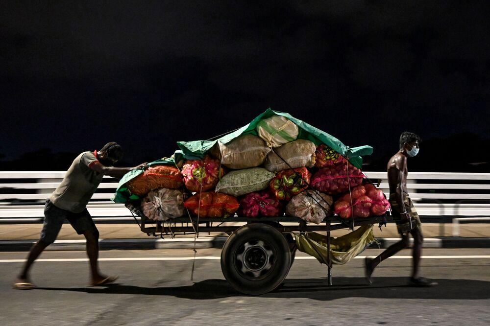 Trabalhadores com máscaras faciais, devido ao coronavírus, levam carrinho de legumes por rua de Colombo, no Sri Lanka, 11 de abril de 2020