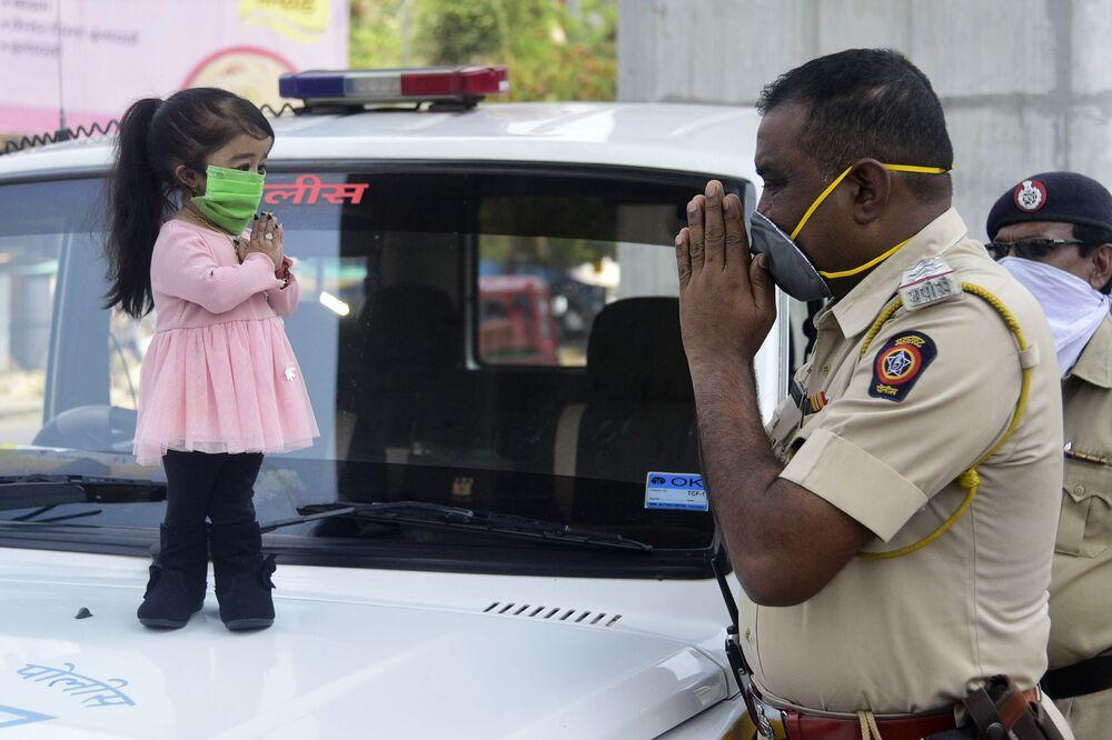 Recordista mundial da menor mulher viva do mundo, Jyoti Amge, cumprimenta policial enquanto apela aos cidadãos para permanecerem em suas casas durante a pandemia do coronavírus, em Nagpur, Índia, 13 de abril de 2020