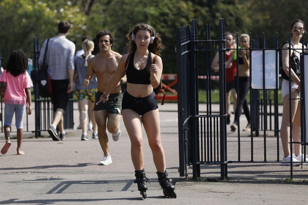 Pessoas se exercitam no Victoria Park, no leste de Londres, 11 de abril de 2020