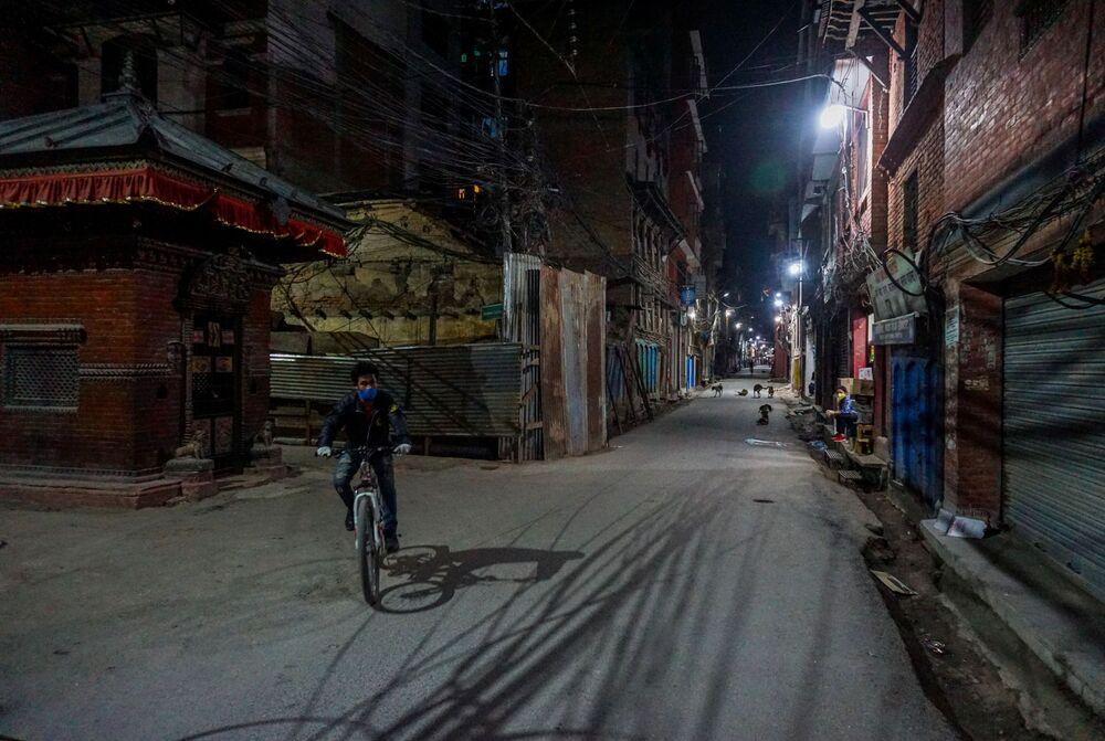 Homem usando máscara de proteção anda de bicicleta em rua na periferia de Katmandu, capital do Nepal