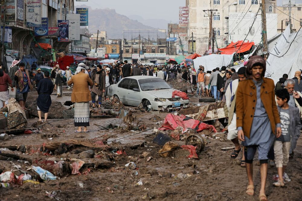 Pessoas caminham em rua danificada em uma área inundada por fortes chuvas em Sanaa, no Iêmen, 14 de abril de 2020