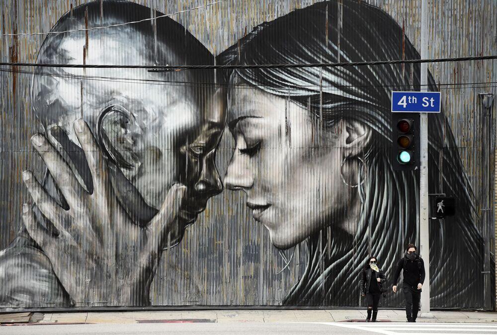 Casal com máscaras passam em frente a muro grafitado em um bairro em Los Angeles, Califórnia, EUA, 10 de abril de 2020