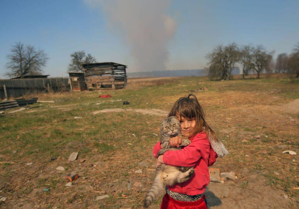 Garota com gato em pátio de casa no vilarejo de Ragovka, em meio ao incêndio na zona de exclusão da usina nuclear de Chernobyl