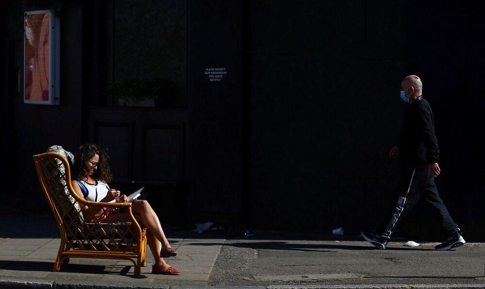Mulher sentada na cadeira em rua de Dalston, Londres, enquanto a propagação do coronavírus continua, Reino Unido, 14 de abril de 2020