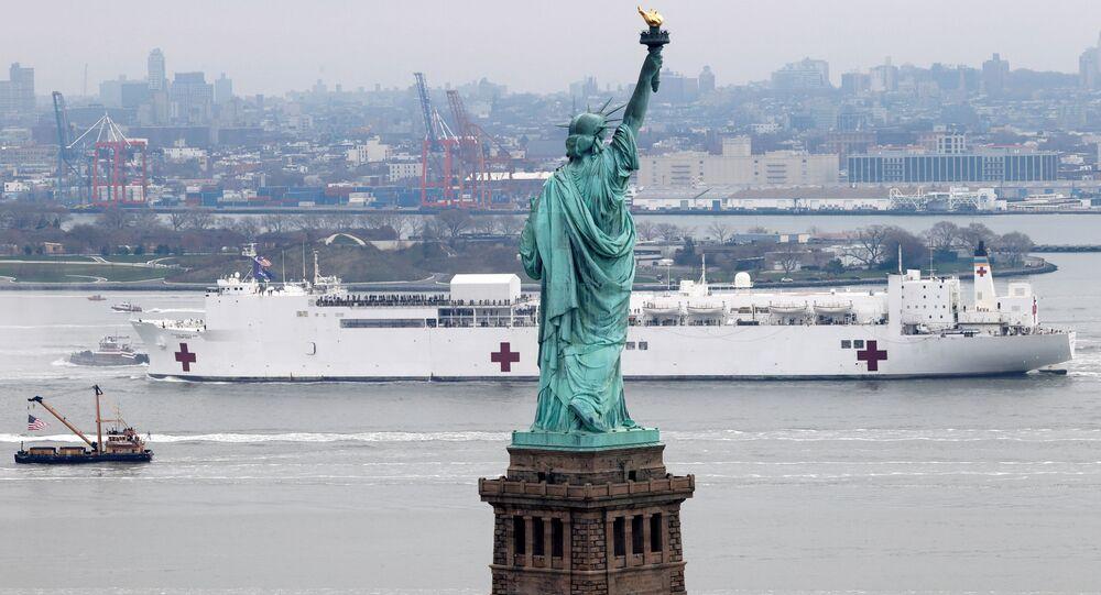 O navio USNS Comfort passando pela Estátua da Liberdade durante o surto da doença do coronavírus na cidade de Nova York, Estados Unidos, 30 de março de 2020