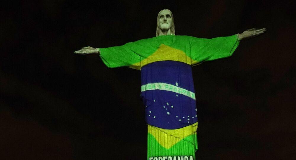 Estátua do Cristo Redentor do Rio de Janeiro é iluminada com a bandeira do Brasil, durante a pandemia do novo coronavírus, no Rio de Janeiro, 12 de abril de 2020
