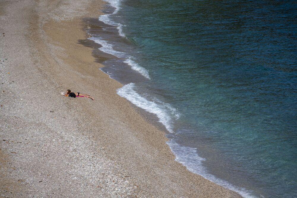 Pessoa toma sol em praia pública, vazia devido à pandemia, na cidade adriática de Medveja, Croácia, 7 de abril de 2020