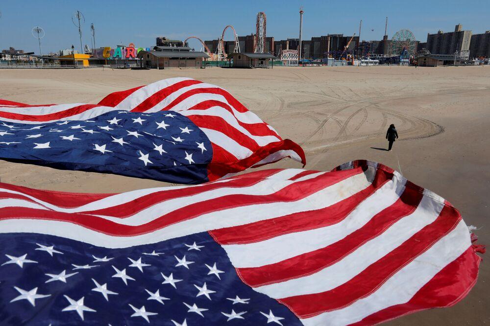 Bandeiras dos Estados Unidos estiradas na praia de Coney Island durante a pandemia do coronavírus no Brooklyn, Nova York, 19 de abril de 2020