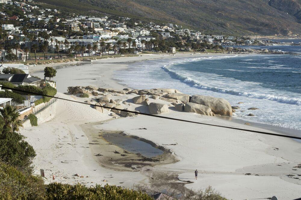 Homem caminha em praia deserta de Camps Bay, na Cidade do Cabo, África do Sul, 10 de abril de 2020