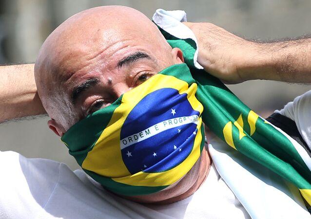 Bolsonarista usa bandeira do Brasil como máscara durante protesto contra a quarentena em São Paulo (SP), 18 de abril de 2020