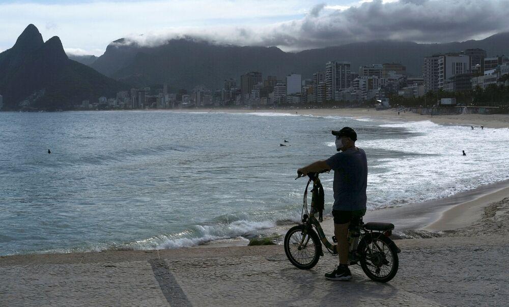 Homem com máscara protetora observa praia do Arpoador durante pandemia do coronavírus no Rio de Janeiro, Brasil, 29 de março de 2020