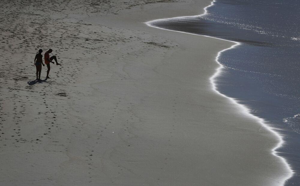 Pessoas se exercitam na praia do Leblon após o fechamento das praias, em meio à pandemia do coronavírus, no Rio de Janeiro, Brasil, 25 de março de 2020
