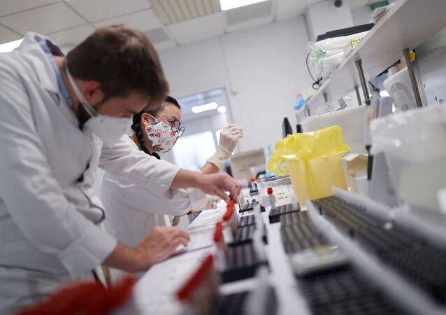 Funcionários de laboratório da França analisam material colido de pessoas com suspeita da COVID-19