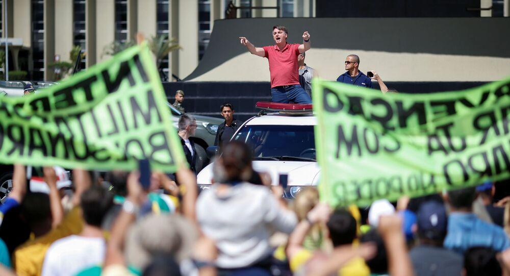 Presidente Jair Bolsonaro gesticula ao falar com seus apoiadores, que participavam de uma comitiva para protestar contra a quarentena e as medidas de distanciamento social, em meio à pandemia do coronavírus, em Brasília, Brasil, 19 de abril de 2020