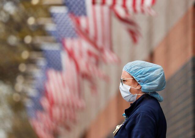 Enfermeira usa máscara protetora enquanto aguarda ambulância em hospital em Nova York, EUA, 20 de abril de 2020