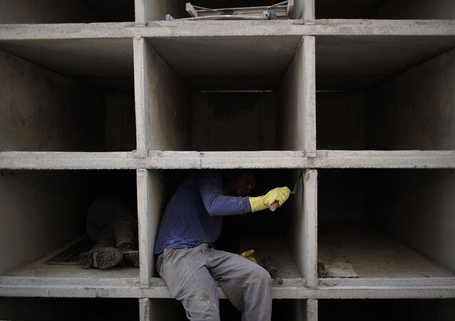 Funcionário constrói novas sepulturas no Cemitério do Caju, no Rio de Janeiro, 20 de abril de 2020