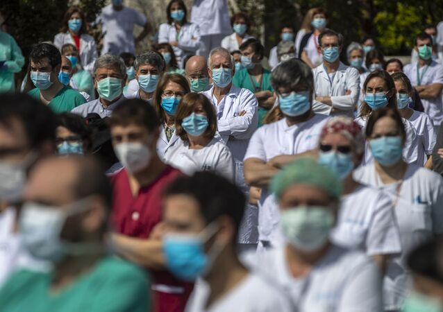 Agentes de saúde fazem um minuto de silêncio pela morte de colega, em Madri, na Espanha, 20 de abril de 2020