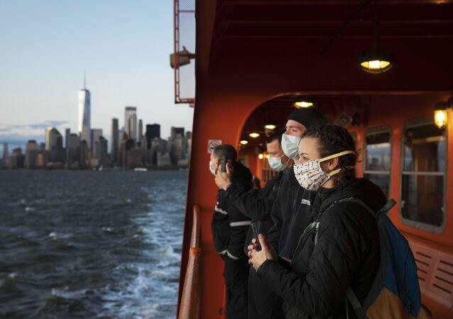 Especialistas médicos com máscaras se direcionando de barca a Nova York para ajudar a combater o coronavírus