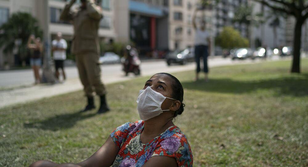 Mulher com máscara observa bombeiro tocando trompete do topo de uma escada para moradores do Rio de Janeiro durante quarentena