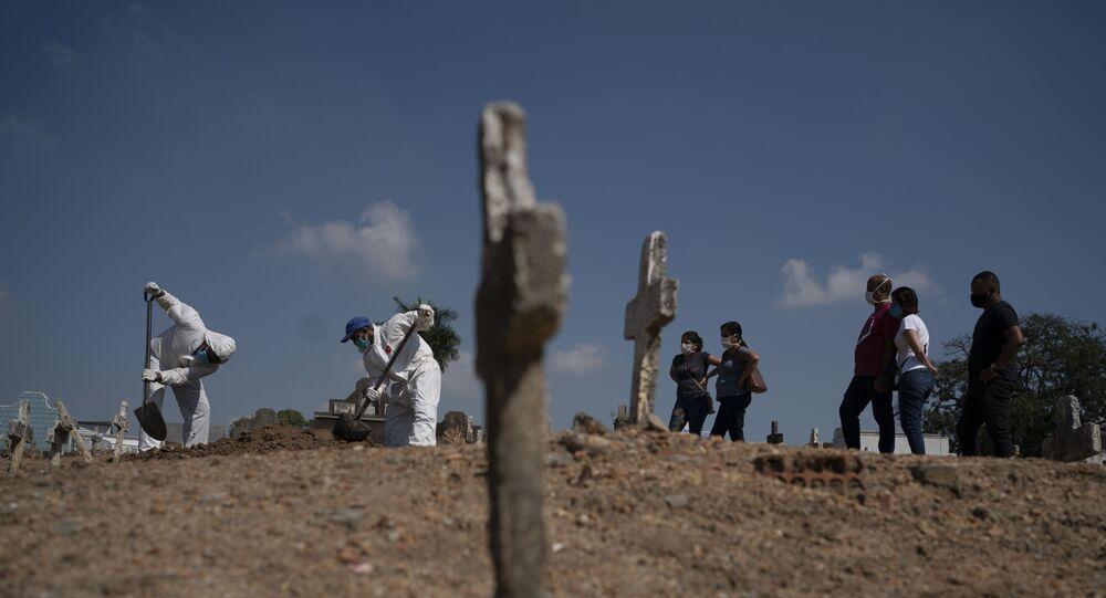 Agentes funerários cobrem caixão de vítima suspeita de ter sido infectada pelo novo coronavírus no Rio de Janeiro.