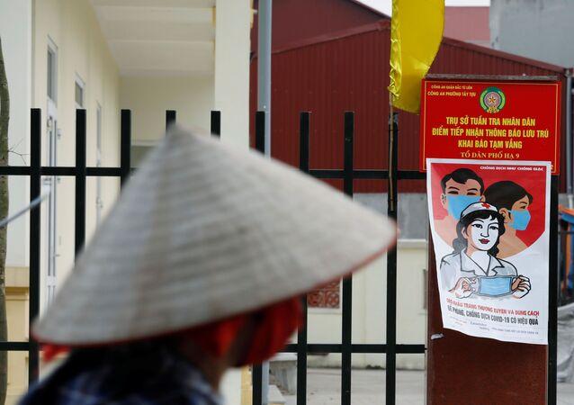 Ciclista próximo a cartaz sobre medidas de prevenção contra a COVID-19, em Hanói, capital do Vietnã, 22 de abril de 2020