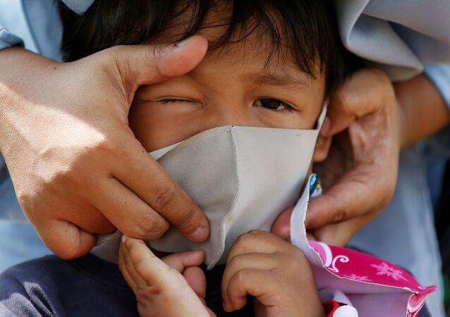 Pessoa ajusta máscara em criança na capital da Indonésia, Jacarta, em meio à pandemia de COVID-19, 23 de abril de 2020