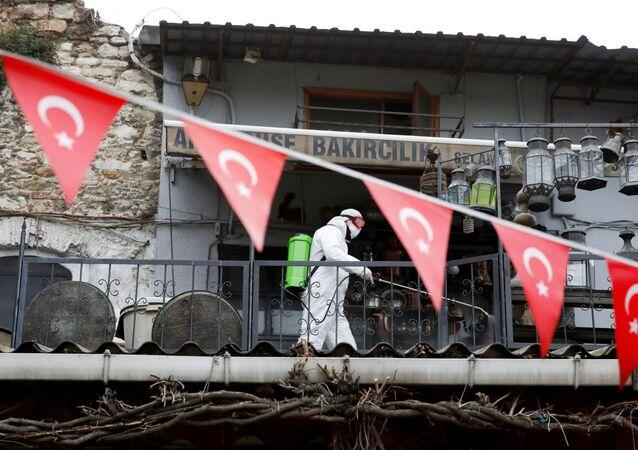 Um trabalhador de traje protetor pulveriza desinfetante no Grande Bazar, conhecido como Bazar Coberto, para prevenir a propagação da doença do coronavírus (COVID-19), em Istambul, Turquia, 25 de março de 2020