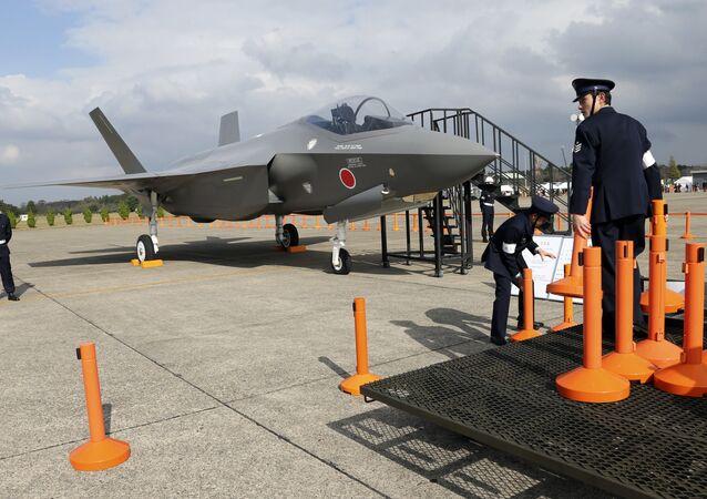 Tripulantes da Força Aérea de Autodefesa do Japão montam delimitadores para proteger uma maquete do jato de caça F-35 durante o evento anual da Força Aérea de Autodefesa na Base Aérea de Hyakuri, a norte de Tóquio, em 26 de outubro de 2014