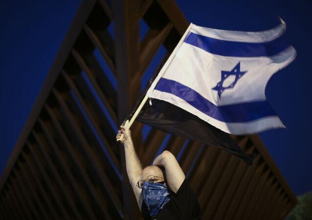 Israelense preocupado com a COVID-19 ostenta uma bandeira do país em Tel Aviv
