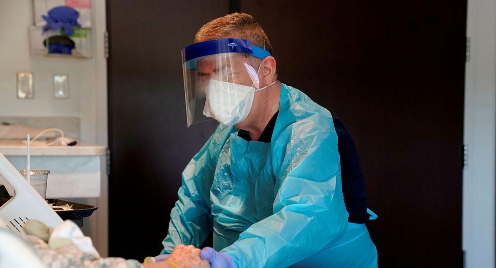 Médico com paciente que espera resultado de teste para a COVID-19, na cidade de Shawnee, no estado de Oklahoma, EUA, 23 de abril de 2020