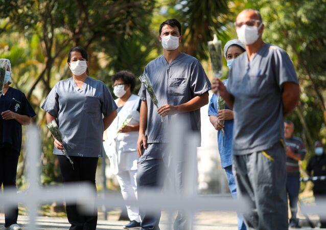 Enfermeiros do Hospital Dr. José Soares Hungria, em São Paulo, durante enterro de seu colega de trabalho, 23 de abril de 2020