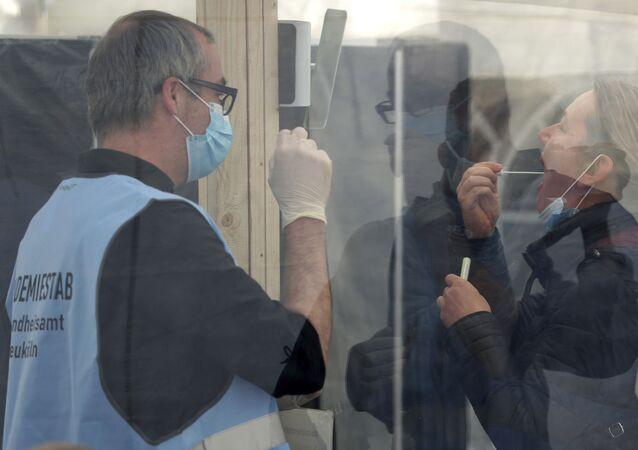 Agente de saúde auxilia mulher a realizar teste do coronavírus em Berlim, na Alemanha