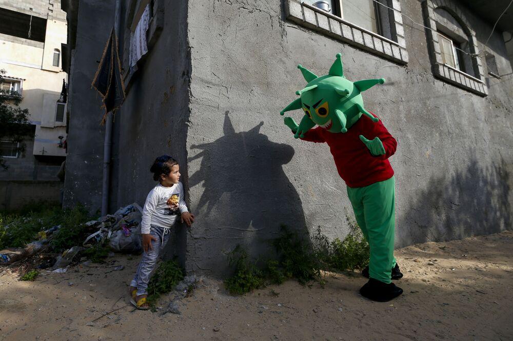 Palestino em fantasia de coronavírus brinca com garotinha na região central da Faixa de Gaza durante a pandemia da COVID-19
