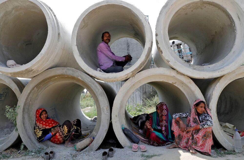 Trabalhadores migrantes descansam em tubulações de cimento durante quarentena na Índia