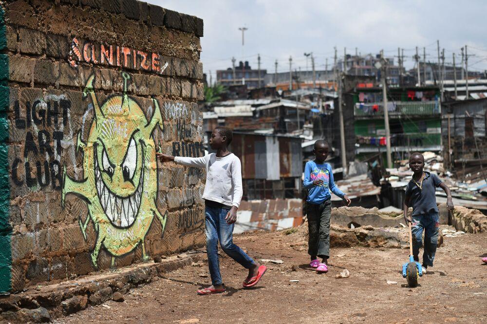 Garoto lê mensagem feita em parede de favela do Quênia com alerta sobre a COVID-19
