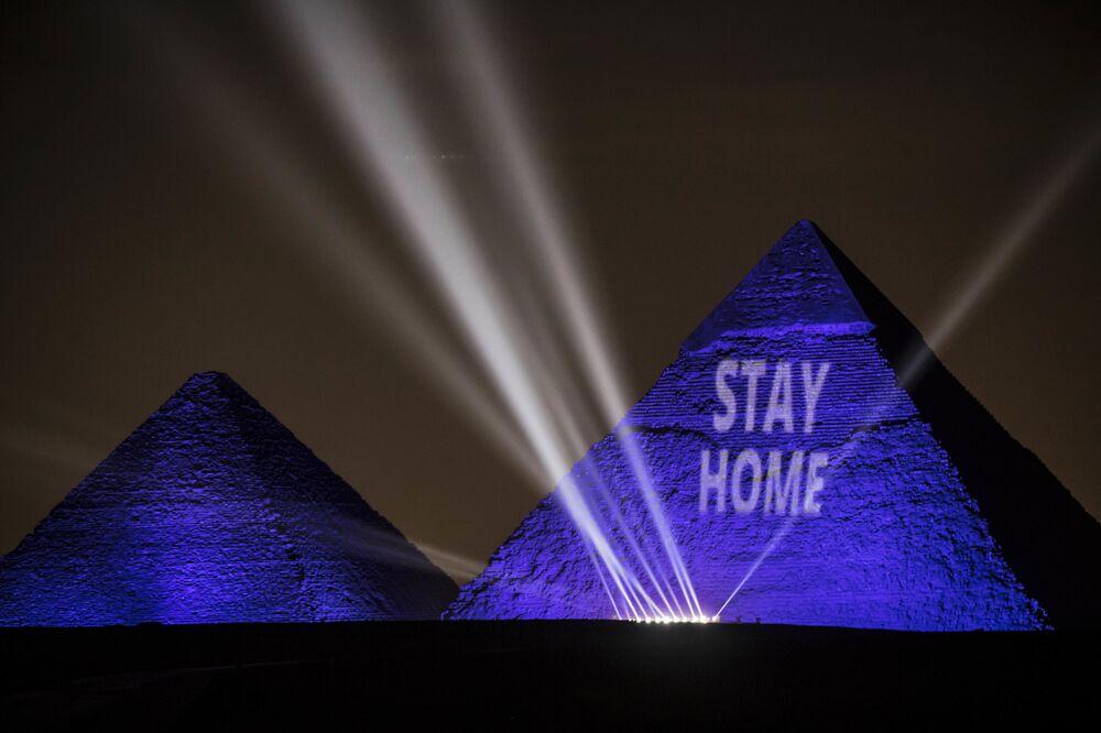 Pirâmides do Egito, no Cairo, refletem slogan da campanha Fique em casa como medida para incentivar a prevenção da COVID-19 no mundo