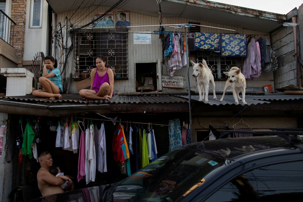 Moças sentadas em telhado de casa junto com seus cachorros durante quarentena na região metropolitana de Manila, Filipinas